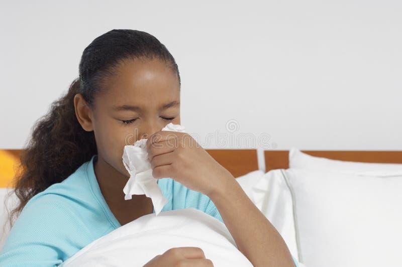 女孩在床上的吹她的鼻子 免版税图库摄影