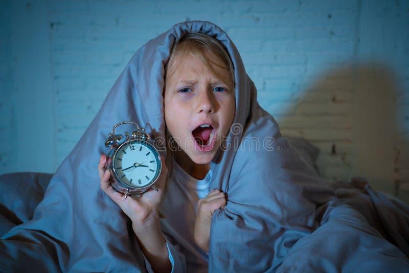 女孩在床上醒在感到的晚上打呵欠和不安定显示时钟她不可能睡觉 库存照片