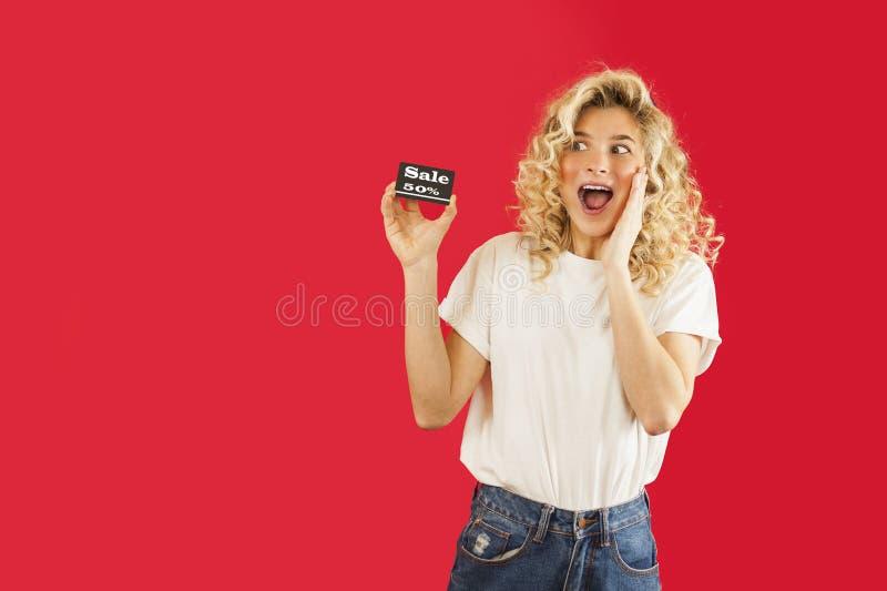 女孩在度假与折扣优惠券的购买的在手上在红色被隔绝的背景 华伦泰` s天,华伦泰` s天 免版税库存照片