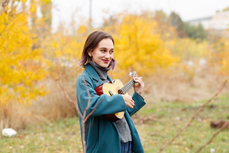 女孩在弹吉他的秋天公园 图库摄影