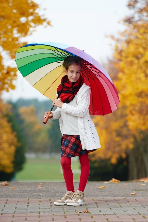 女孩在彩虹伞下在秋天公园 免版税库存照片