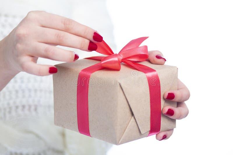 女孩在手上的拿着一个礼物,打开箱子的妇女包裹在白色被隔绝的背景,概念寒假的工艺纸 库存图片