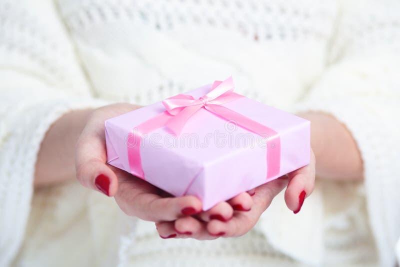 女孩在手上的拿着一个礼物,有在白色被隔绝的背景,概念冬天的装饰桃红色纸包裹的礼物盒的妇女 库存图片