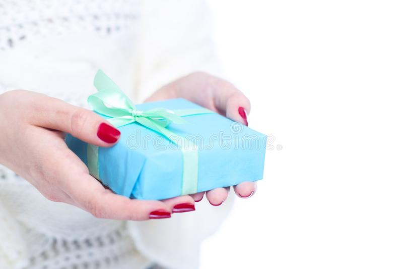 女孩在手上的拿着一个礼物,有在白色被隔绝的背景,概念冬天的装饰纸包裹的礼物盒的妇女 免版税图库摄影