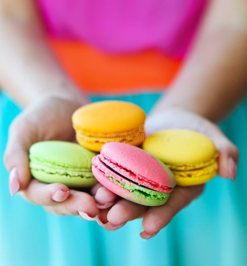女孩在手上的拿着五颜六色的蛋白杏仁饼干 免版税库存图片