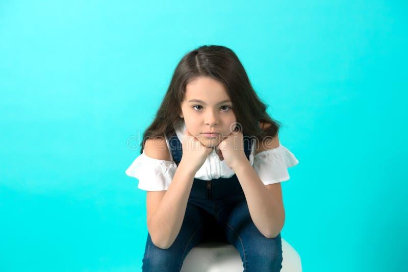 女孩在手上的支柱下巴在蓝色背景 免版税库存照片