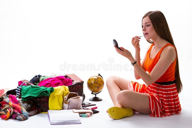 女孩在手提箱附近坐 库存图片