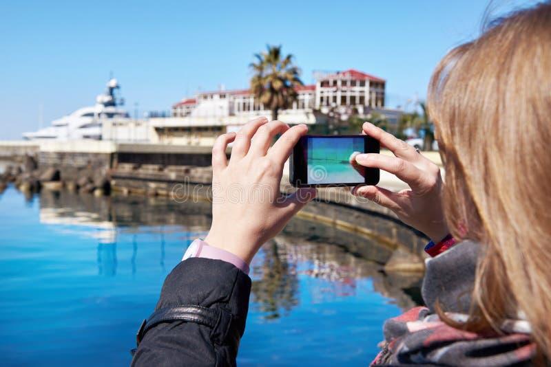 女孩在手机海滨和码头拍摄 免版税库存图片