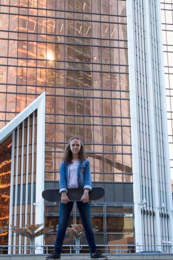 女孩在拿着一个冰鞋板的大厦附近站立在城市在一个高楼附近 免版税库存图片