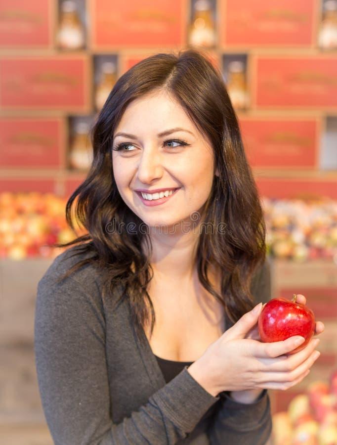 女孩在拿着一个红色苹果的杂货店,当微笑时 免版税图库摄影