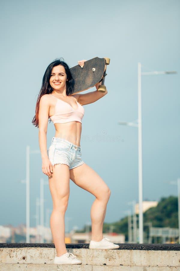 女孩在拿着在她的肩膀的晴天站立滑板 图库摄影