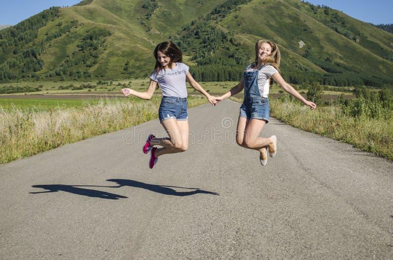 女孩在握手的路跳 免版税库存照片