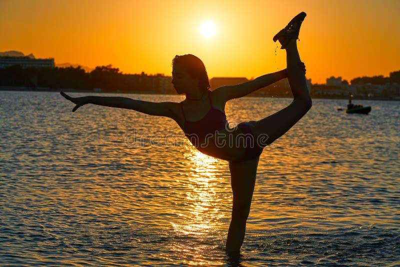 女孩在日落海滩的体操姿势 库存图片
