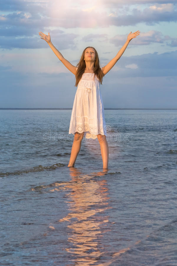 女孩在日落的海向太阳说再见 免版税库存图片