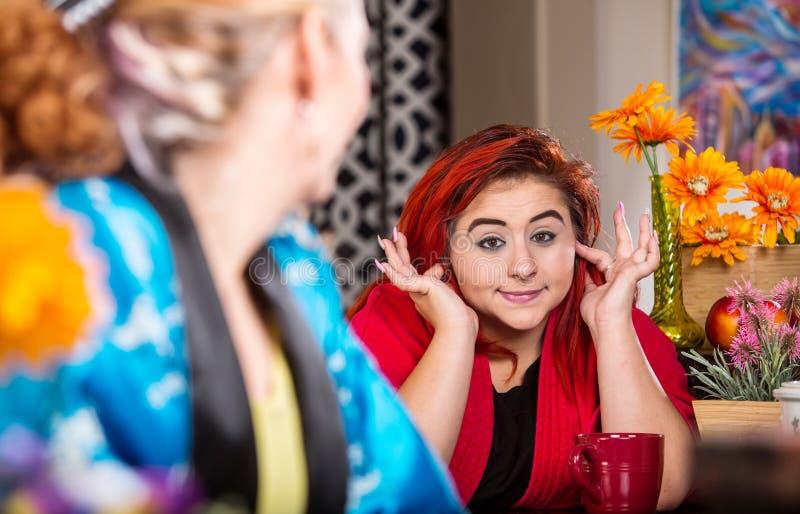 女孩在明亮地色的厨房里忽略母亲 图库摄影