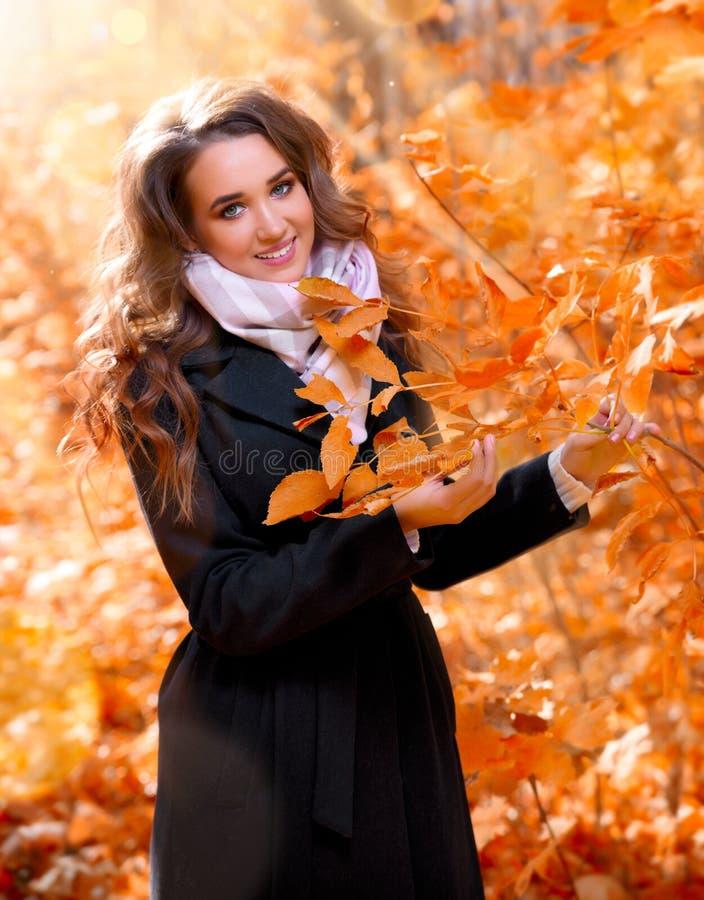 女孩在晴朗的秋天森林里 库存照片