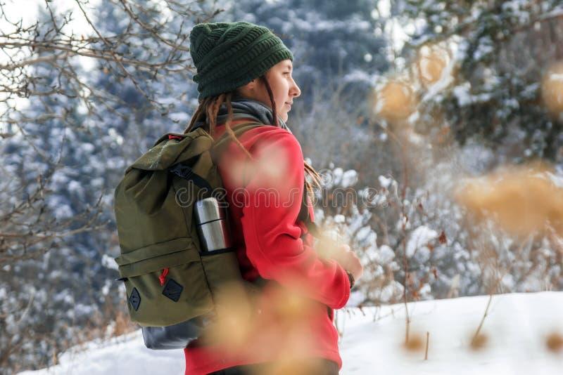 女孩在有一个绿色背包的冬天森林里 库存图片