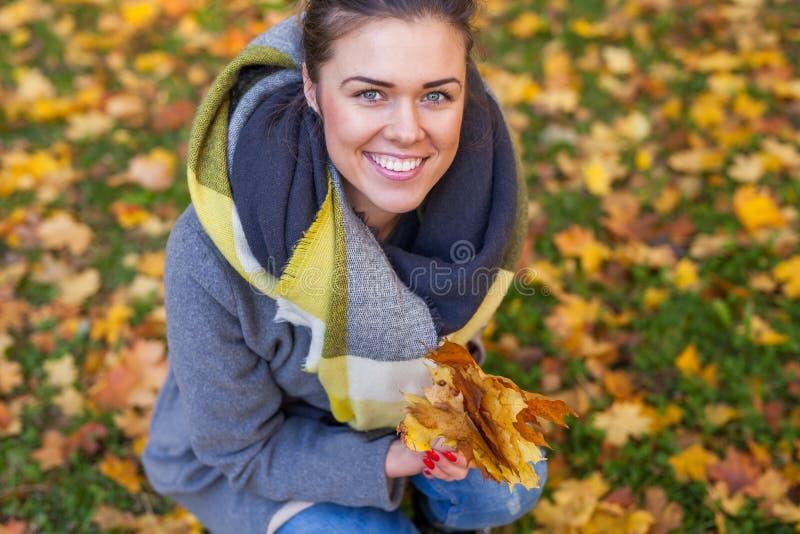 女孩在有叶子花束的公园  秋天时间 库存图片