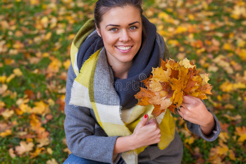 女孩在有叶子花束的公园  秋天时间 库存照片