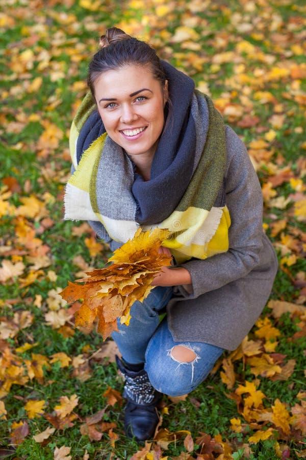 女孩在有叶子花束的公园  秋天时间 免版税库存图片