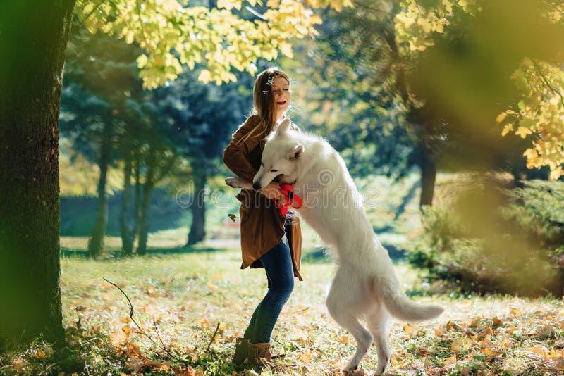 女孩在有幼小白色瑞士牧羊犬的秋天公园走 图库摄影