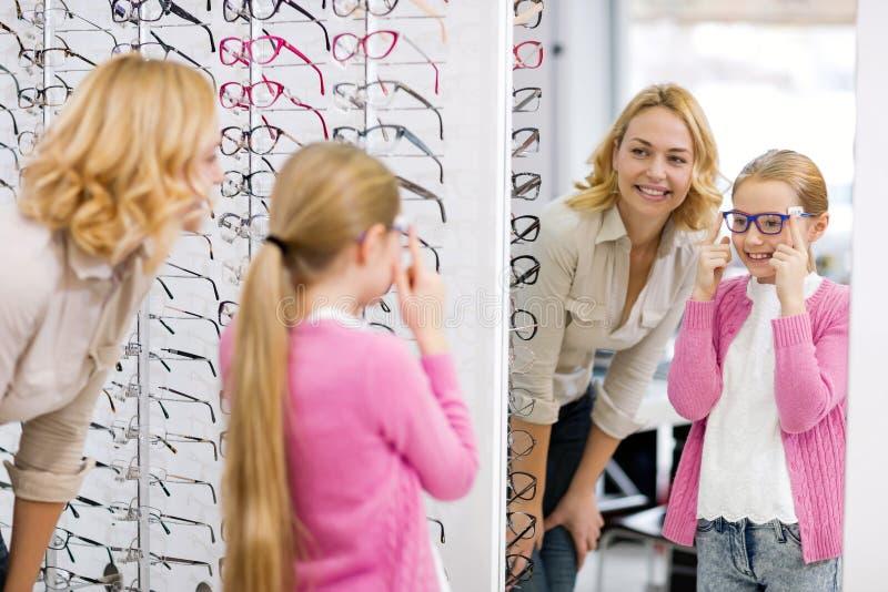 女孩在有新的eyewear的镜子看自己 免版税库存照片