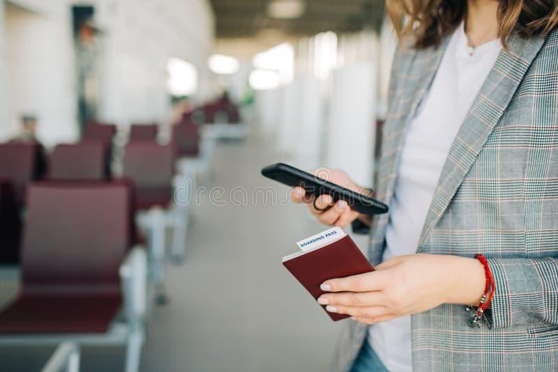 女孩在有智能手机和护照的机场 免版税库存图片