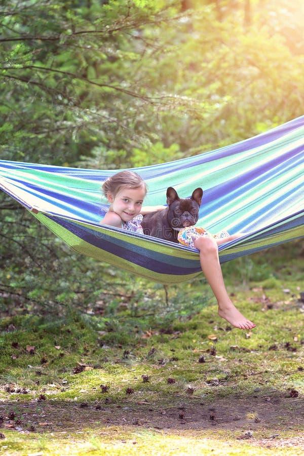 女孩在有狗的一个吊床使用 库存照片