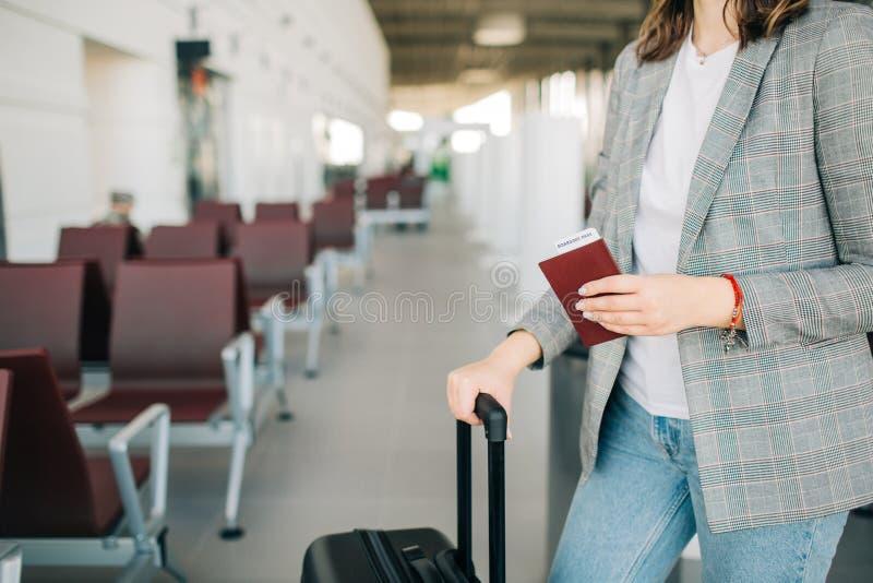 女孩在有行李和护照的机场 免版税库存图片