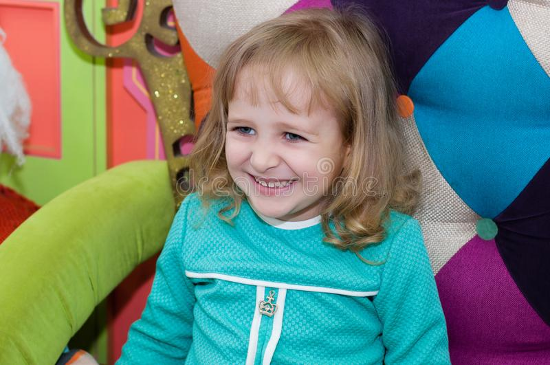女孩在有雪人的一把扶手椅子坐在购物中心 库存图片
