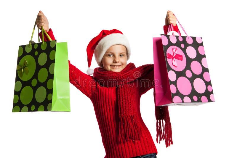 女孩在有购物袋的圣诞老人帽子 免版税库存照片