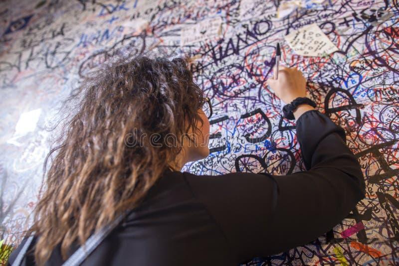 女孩在朱丽叶墙壁写爱消息  在砖田鼠朱丽叶的房子的街道画在维罗纳 墙壁盖充满爱 免版税库存照片