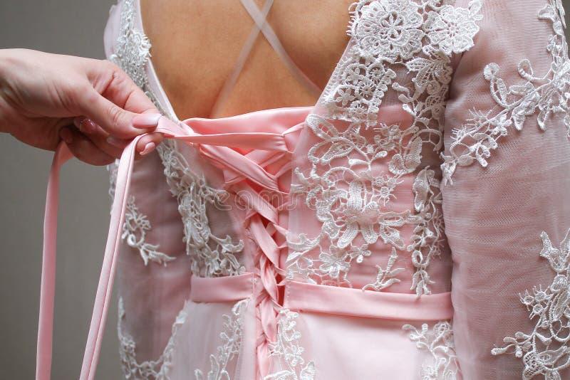 女孩在束腰的被打结的桃红色礼服 免版税库存照片