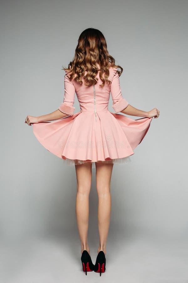 女孩在桃红色礼服藏品装饰了衣裙在灰色背景的裙子 库存照片
