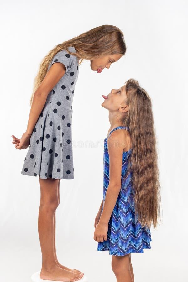 女孩在椅子站立,另一个女孩站立附近,互相显示舌头 免版税库存图片