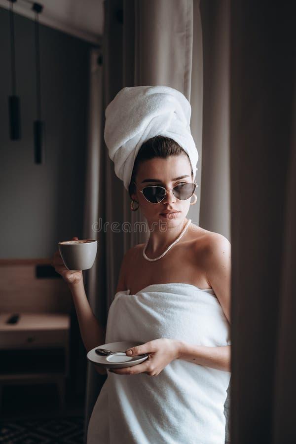 女孩在毛巾饮用的咖啡包裹了 库存照片