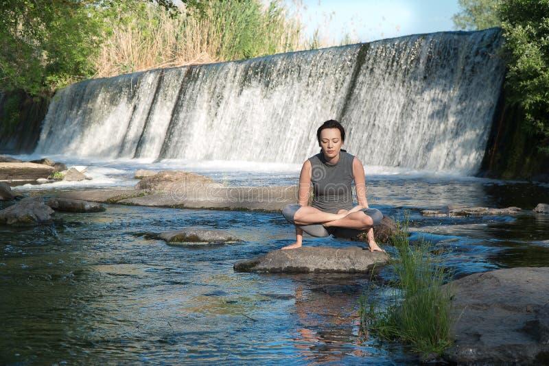 女孩在水边练瑜伽 免版税库存图片