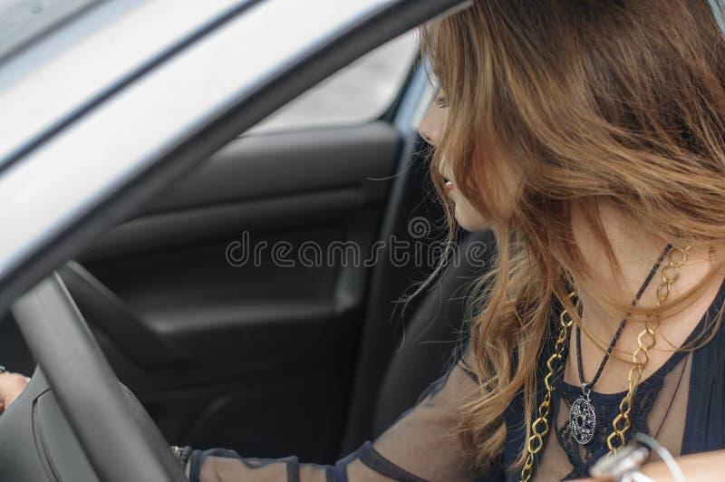 女孩在汽车坐作为司机 库存图片