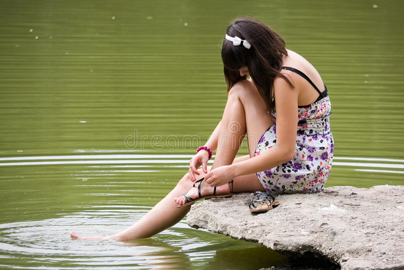 女孩在河坐 免版税库存照片