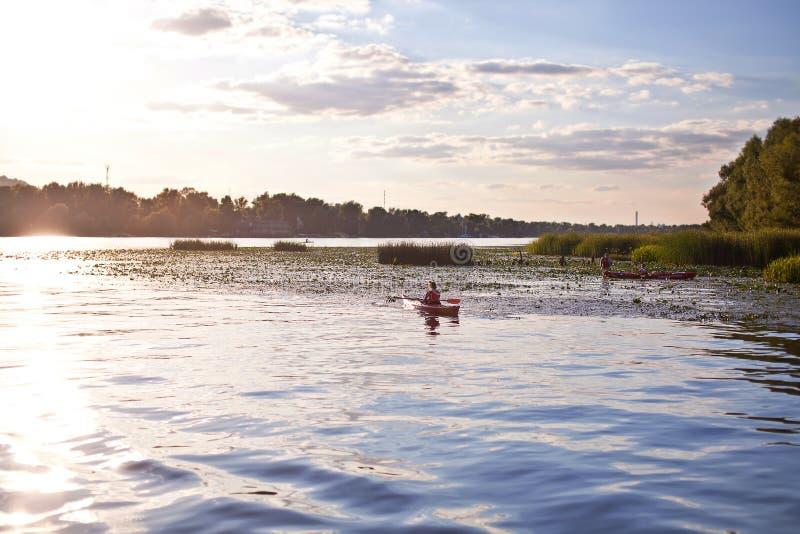 女孩在河的一艘皮船游泳在日落 库存照片