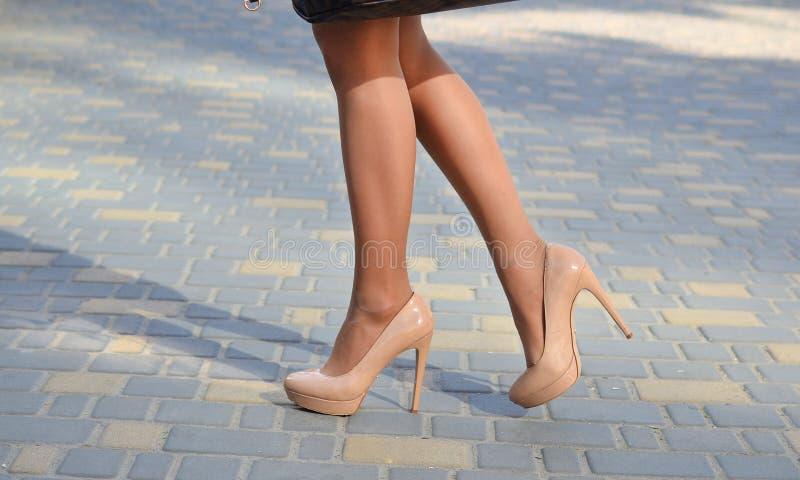 女孩在沿街道的脚跟走 在脚跟特写镜头的女性腿 库存照片