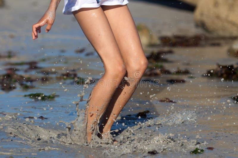 女孩在泥泞的水中跳 库存照片