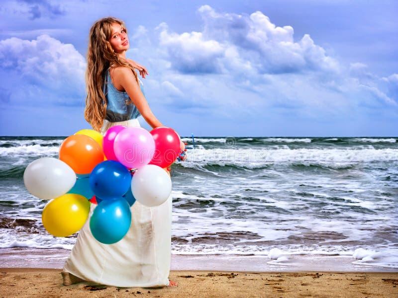 女孩在海海滩保留色的气球走 免版税库存图片