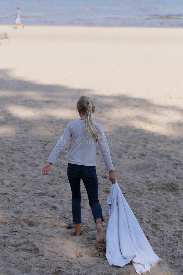 女孩在海滩沙子去 免版税库存照片