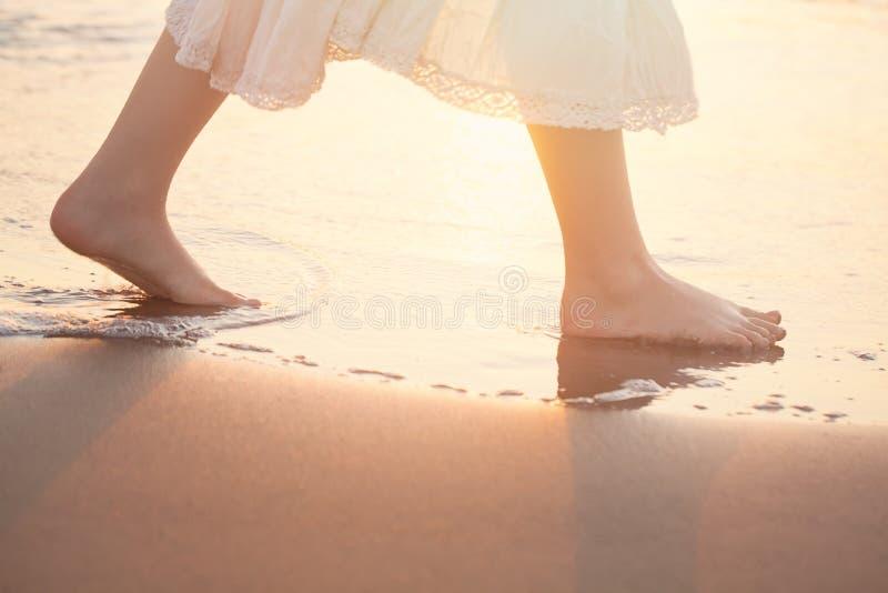 女孩在海滩在水中赤足走 免版税图库摄影
