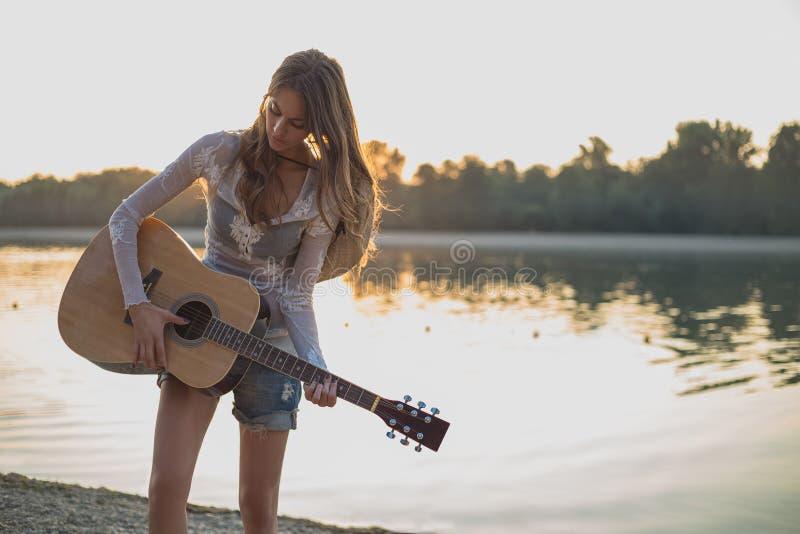 女孩在海滩的持续吉他 免版税库存照片