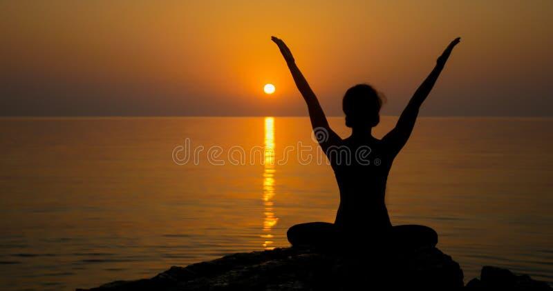 女孩在海洋附近实践瑜伽 图库摄影
