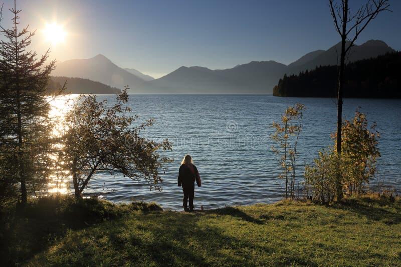 女孩在湖附近站立 免版税库存图片