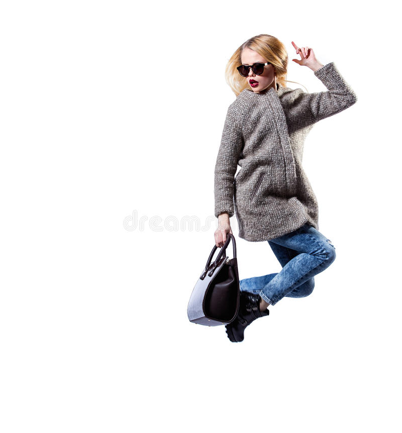 女孩在灰色皮大衣、佩带的太阳镜和黑袋子穿戴了,摆在白色背景 白肤金发性感的秀丽的时尚 免版税库存图片