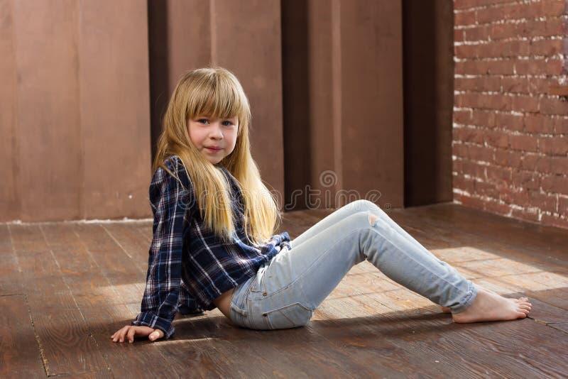 女孩在牛仔裤的6岁坐地板 免版税库存图片